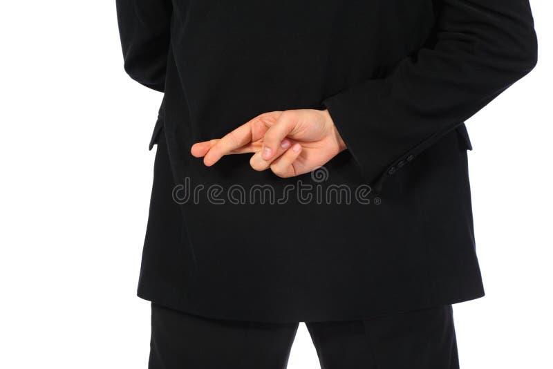 De zakenman met vingers kruiste achter zijn rug