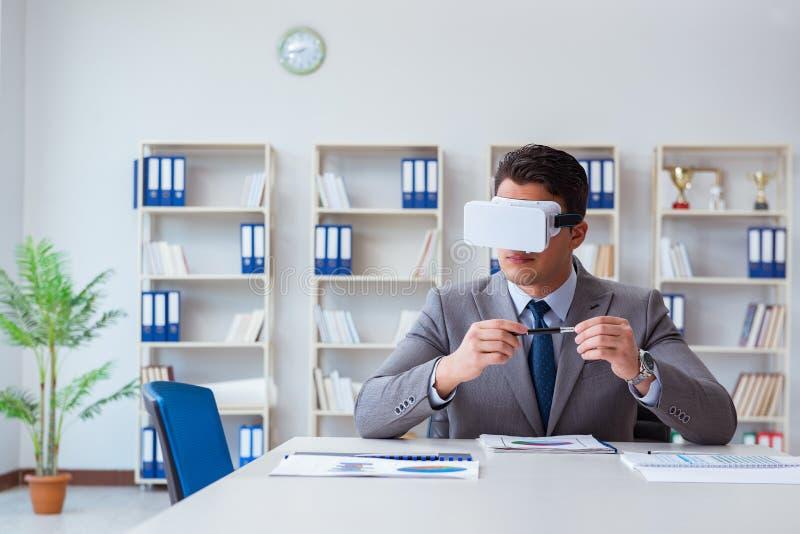 De zakenman met virtuele werkelijkheidsglazen in het bureau stock foto's