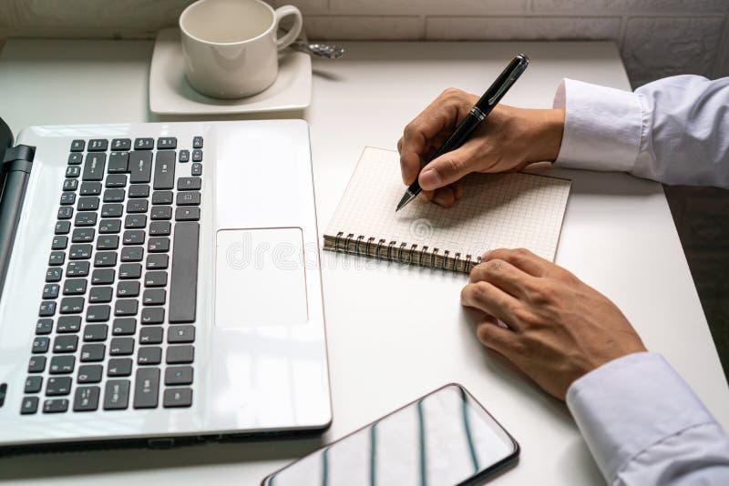De zakenman neemt een nota over het notitieboekje van de financiële informatie royalty-vrije stock foto's