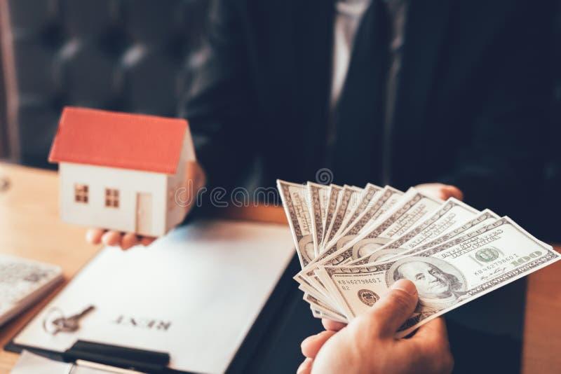De zakenman overhandigde het huis model en nieuwe huiseigenaar die geld geven aan onroerende goederen handel stock foto's
