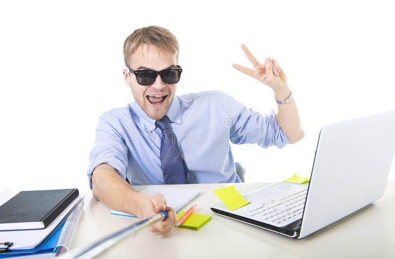 De zakenman in overhemd en bandzitting bij het bureauholding van de bureaucomputer selfie plakt het schieten van zelfportretfoto royalty-vrije stock fotografie