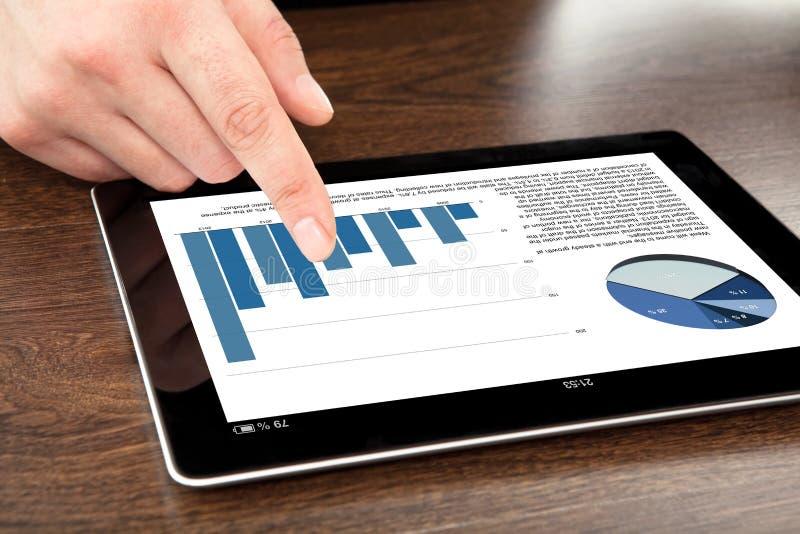 De zakenman richt zijn vinger op een tablet met grafiek  stock afbeelding