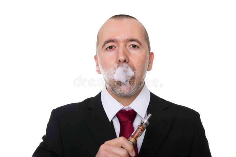 De zakenman rookt een elektronische sigaret stock afbeeldingen