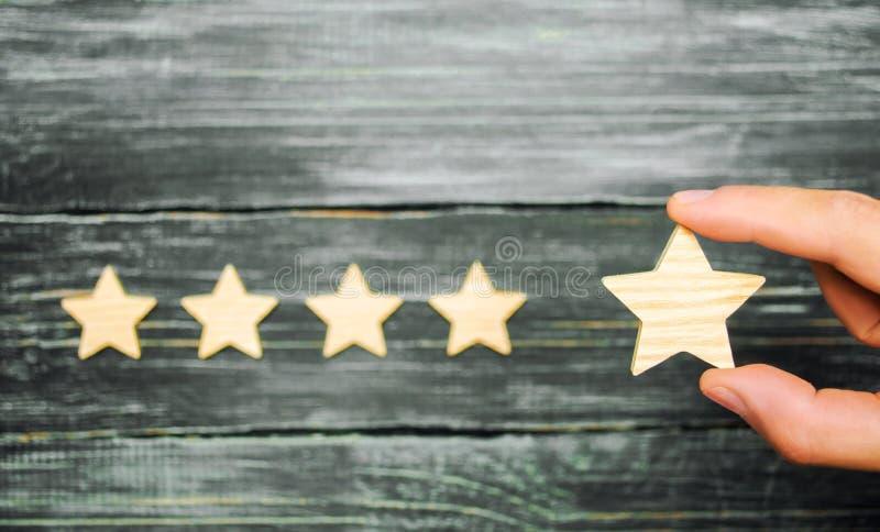 De zakenman` s hand houdt de vijfde ster Een nieuwe ster, voltooiing Het concept de classificatie van hotels en restaurants, Eva stock foto's