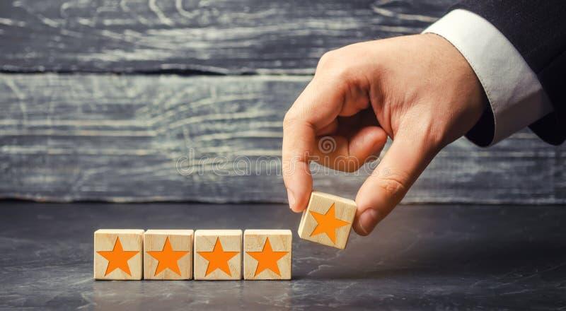 De zakenman` s hand houdt de vijfde ster Krijg de vijfde ster Het concept de classificatie van hotels en restaurants, evaluat stock afbeelding