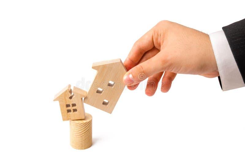 De zakenman` s hand vervangt het oude huis met beschadigde voor nieuwe  Vernieuwing en vernieling voor de bouw concept royalty-vrije stock afbeelding