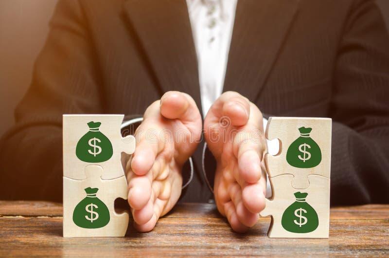 De zakenman scheidt het houten raadsel met een beeld van geld Het concept financieel beheer en distributie van fondsen stock foto