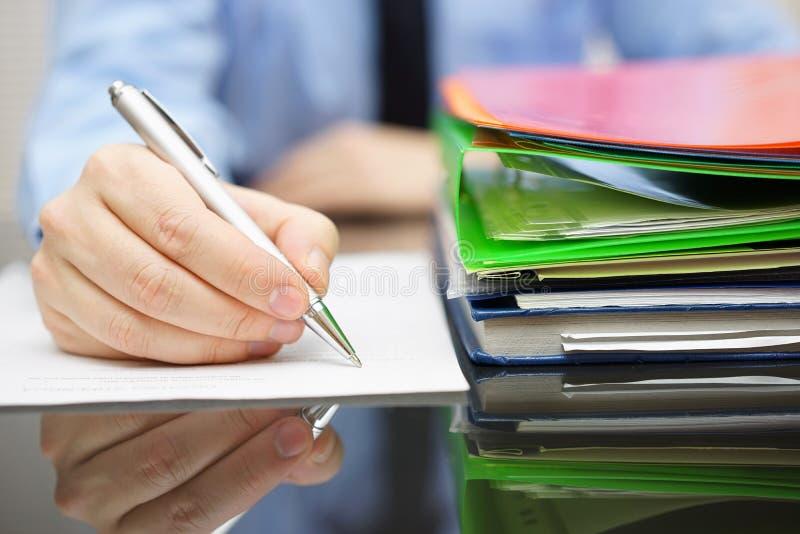 De zakenman schrijft op document en heel wat documentatie is stock foto