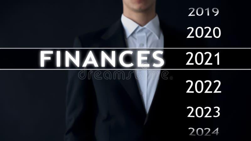 De zakenman selecteert de financiën van 2021 rapporteert over het virtuele scherm, geldstatistieken stock fotografie
