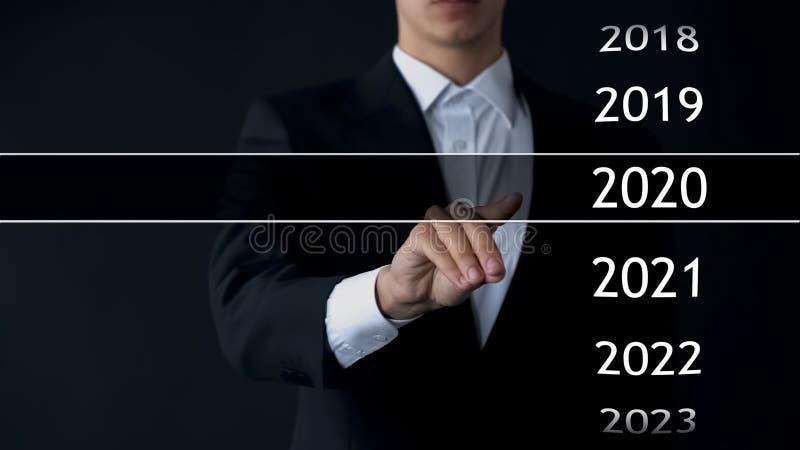 De zakenman selecteert het jaar van 2020 in virtueel menu, onderzoek naar gegevens, bedrijfsgeschiedenis stock afbeeldingen