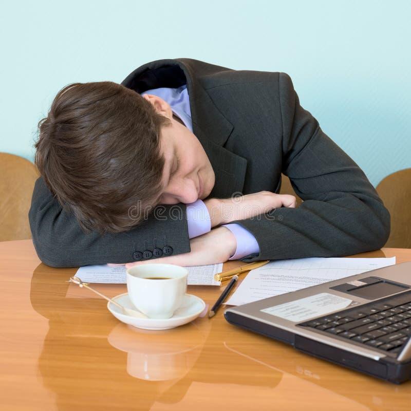 De zakenman is in slaap zitting gevallen op vergadering stock fotografie