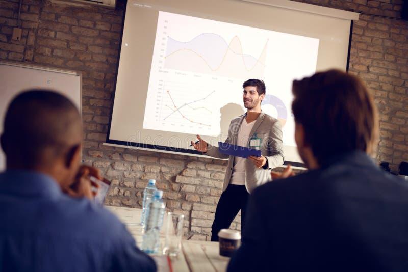 De zakenman spreekt op seminarie aan boord gebruikend gegevens en snijbieten royalty-vrije stock foto