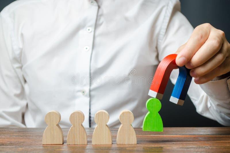 De zakenman trekt een groen cijfer van het team met een magneet De efficiency en de productiviteit van het verhogingsteam identif royalty-vrije stock foto's