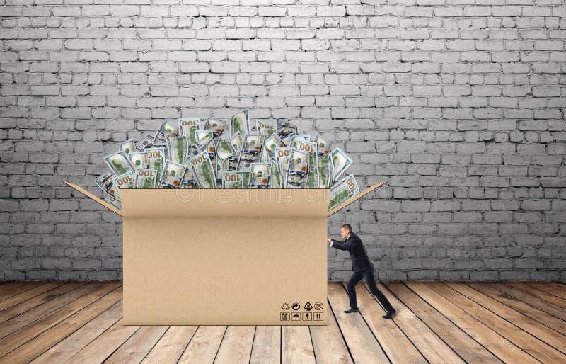 De zakenman trekt een reusachtige doos geld voor hem op de achtergrond van bakstenen muur en houten vloer stock foto's