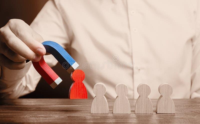 De zakenman trekt een rood cijfer van het team met een magneet De efficiency en de productiviteit van het verhogingsteam royalty-vrije stock afbeeldingen