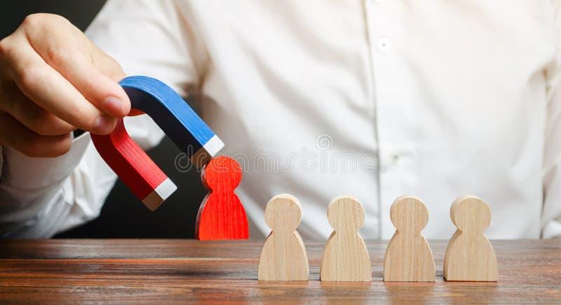 De zakenman trekt een rood cijfer van het team met een magneet de leider beheert de zaken en vormt een team Het concept gifstof stock afbeelding