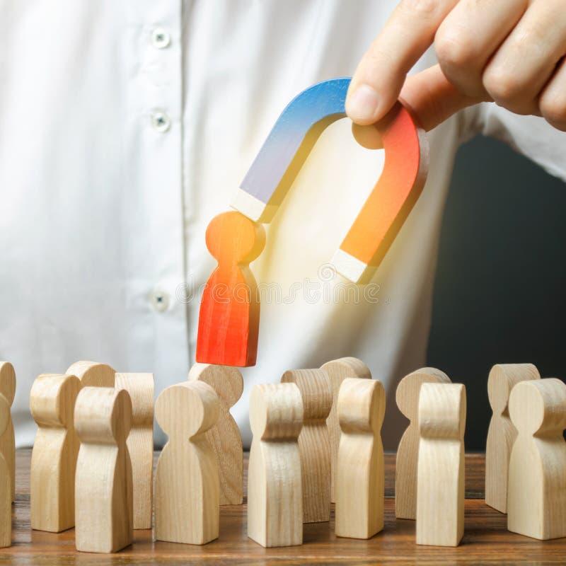 De zakenman trekt een rood cijfer van een mens van de menigte met een magneet terug De efficiency van het verhogingsteam, product royalty-vrije stock afbeelding