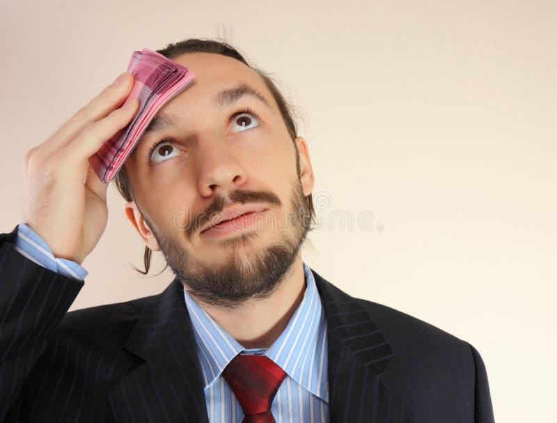 De zakenman veegt langs een voorhoofd af stock fotografie