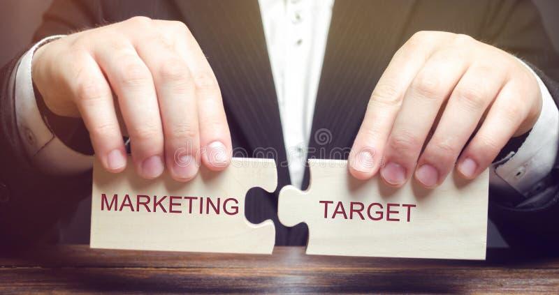 De zakenman verzamelt houten raadsels met het woord Marketing doel Segmentatie van de markt Fragmentatie van consumenten in stock foto
