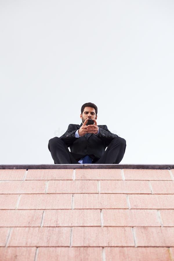 De zakenman verzendt SMS stock foto