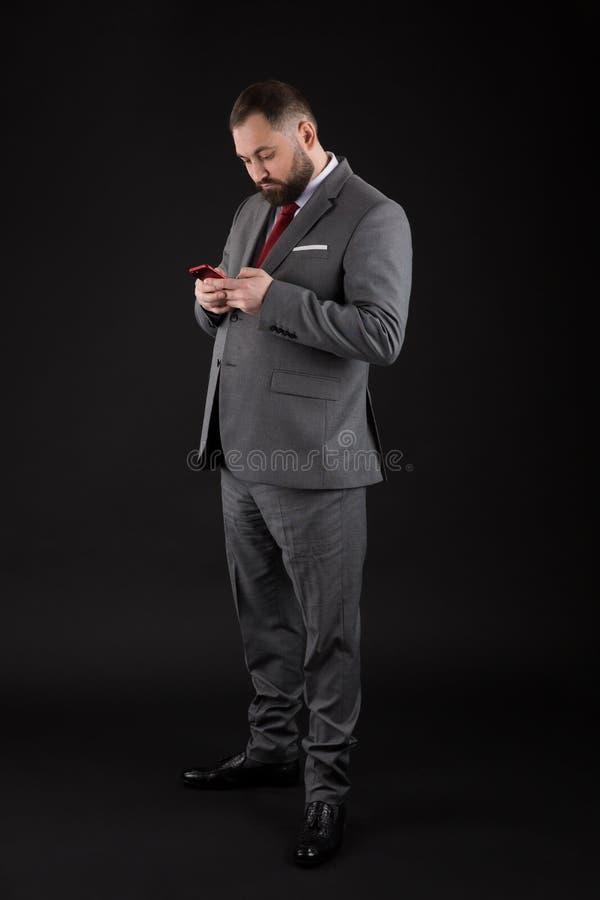 De zakenman verzorgde goed smartphone van de mensengreep Van het gebruikssmartphone van het mensen de formele kostuum sociale net stock afbeeldingen