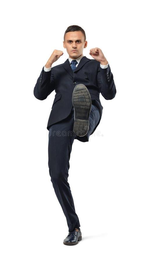 De zakenman volledig-hoogte die direct in camera met zijn benen in het schoppen kijken stelt geïsoleerd op witte achtergrond stock afbeeldingen