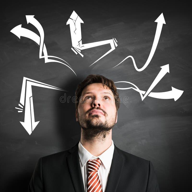De zakenman voor een bord heeft vele ideeën stock afbeelding