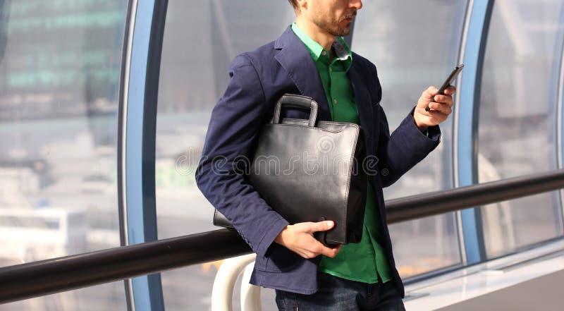 De zakenman in vrijetijdskleding met in leerzak en de cel telefoneren binnen de moderne bureaubouw Jonge stedelijke professionele stock afbeelding