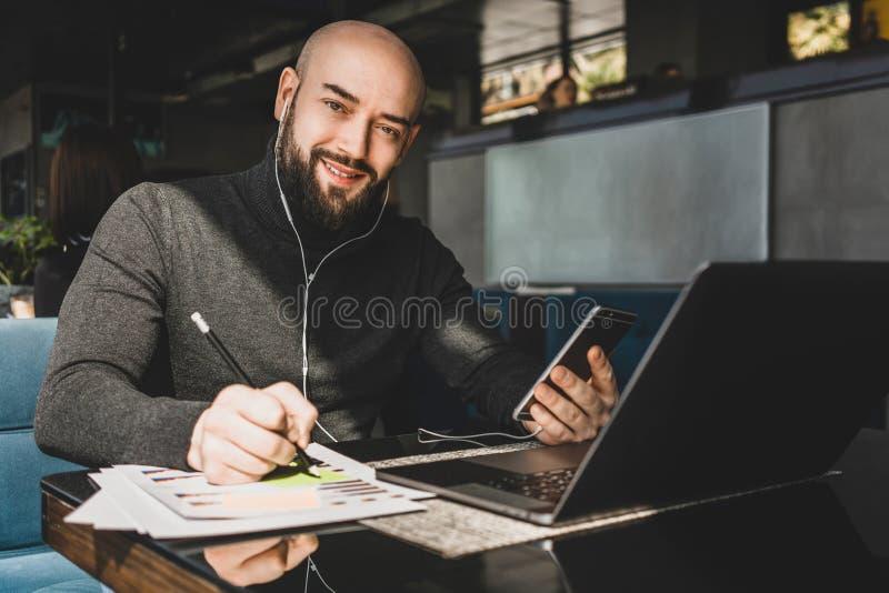 De zakenman werkt aan laptop, makend nota's in document, spreekt in hoofdtelefoons op celtelefoon terwijl het zitten bij lijst in stock fotografie