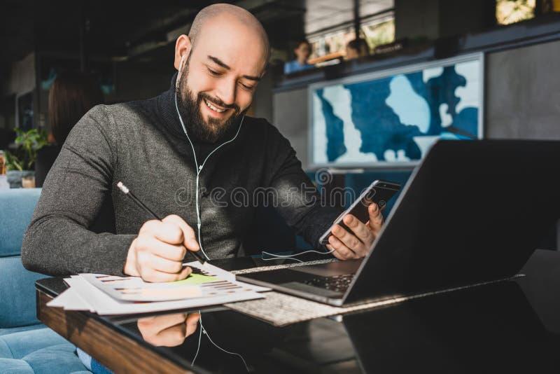 De zakenman werkt aan laptop, makend nota's in document, spreekt in hoofdtelefoons op celtelefoon terwijl het zitten bij lijst in stock afbeelding
