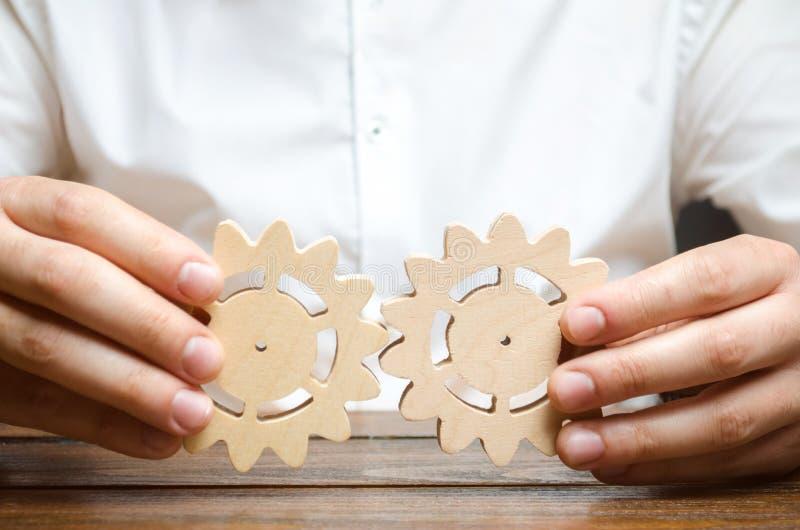 De zakenman in wit overhemd verbindt twee houten toestellen Symboliek van het vestigen van bedrijfsprocessen en mededeling improv stock afbeelding