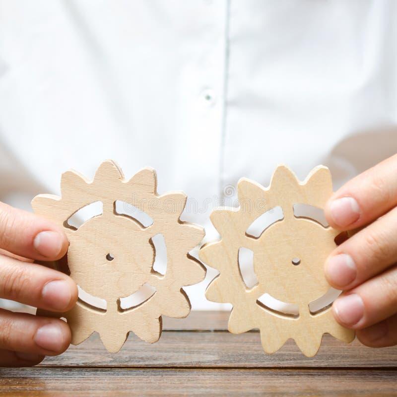 De zakenman in wit overhemd verbindt twee houten toestellen Verbeterend het werkefficiency, die nieuwe verbindingen en leverancie stock foto