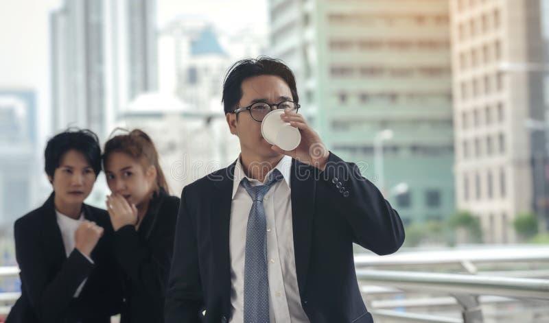 De zakenman wordt door een collega geraakt die achter hem roddelen royalty-vrije stock foto's