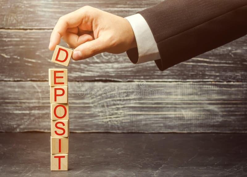 De zakenman zet houten blokken met de woordstorting Concept het investeren van geld in een bank bij een percentage Rentevoeten A stock fotografie
