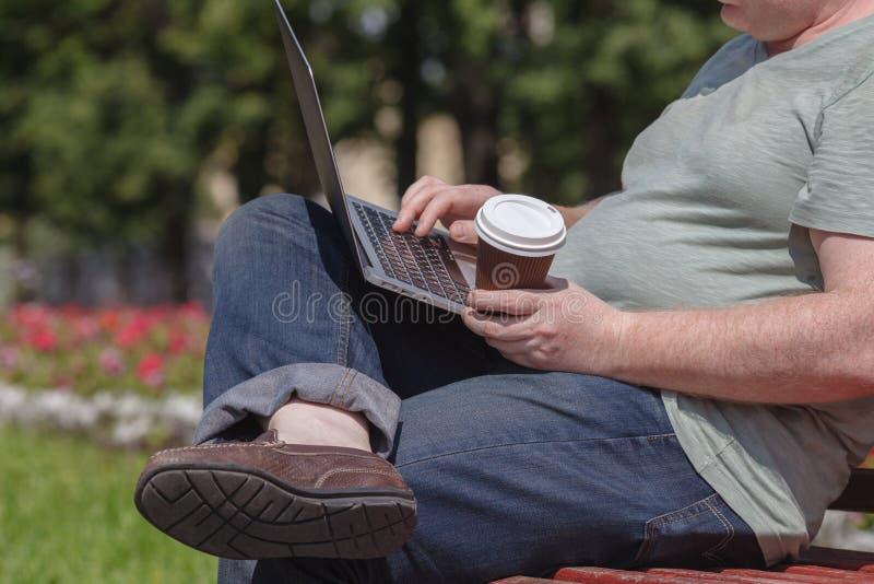 De zakenman zit bij het park en gebruikt laptop Zakenman die openlucht laptop met behulp van stock afbeeldingen