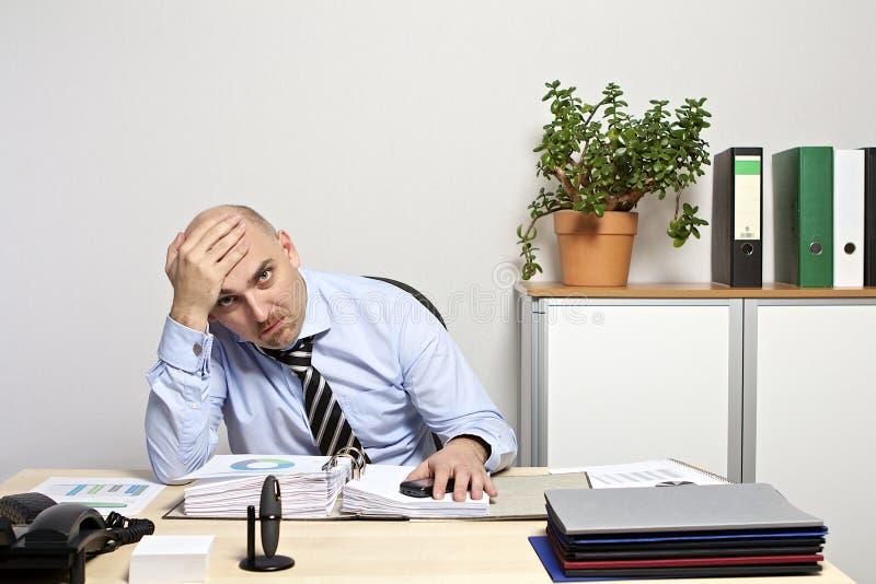 De zakenman zit listlessly, en gefrustreerd bij zijn bureau royalty-vrije stock afbeeldingen