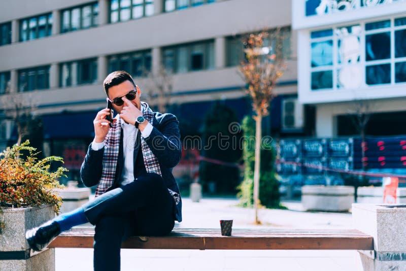 De zakenman zit op bank in het stadscentrum en spreekt op zijn mobiel stock fotografie