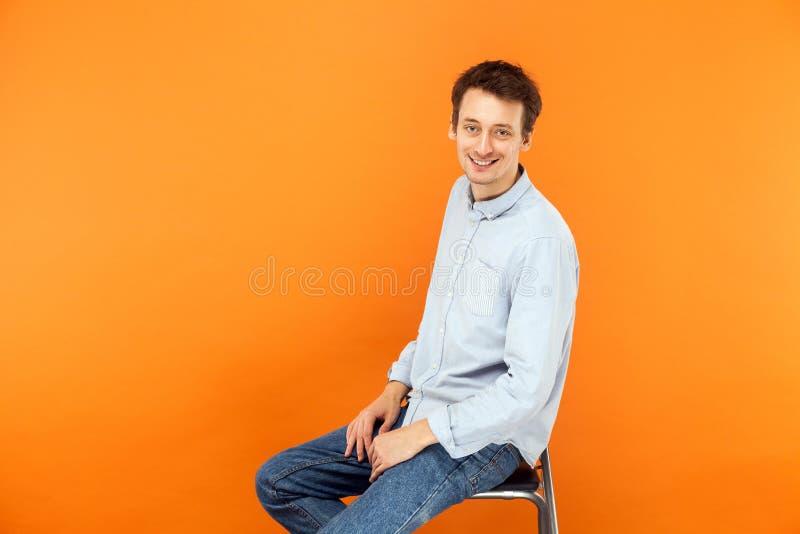 De zakenman zit op stoel, bekijkend camera en toothy glimlach stock foto