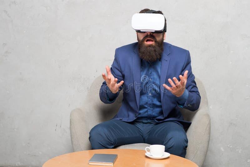 De zakenman zit stoelslijtage hmd onderzoekt virtuele werkelijkheid of AR De partner werkt in virtuele werkelijkheid op elkaar in stock fotografie