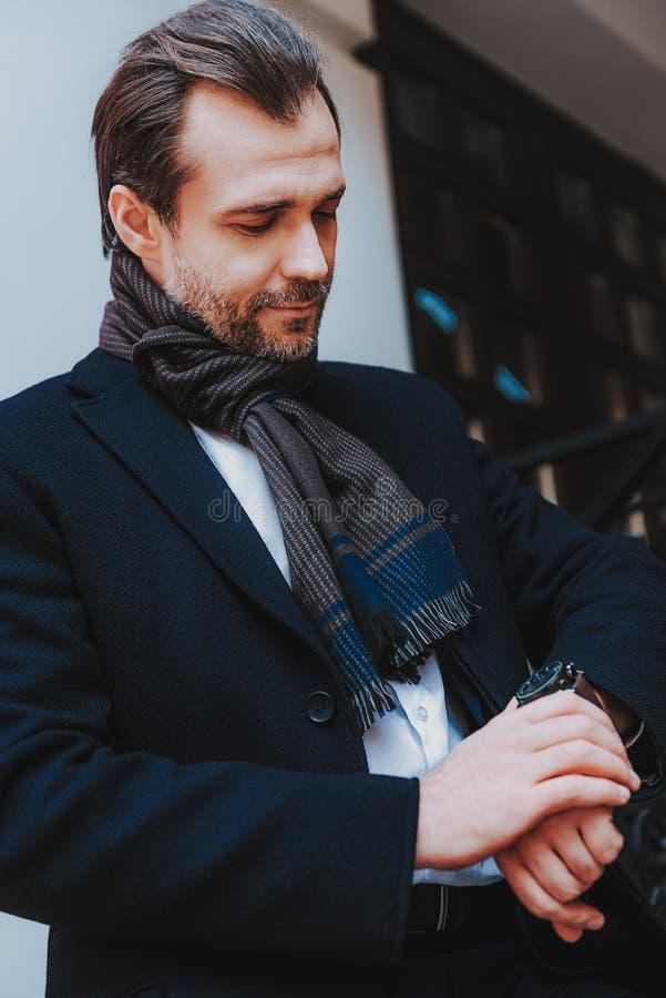 De in zakenman in zwarte laag controleert tijd royalty-vrije stock afbeeldingen