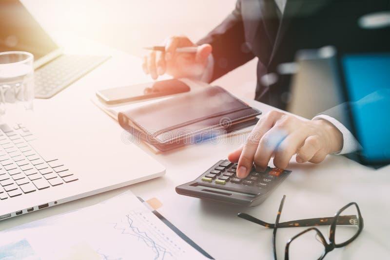 de zakenmanhand die met financiën over kosten werken en berekent royalty-vrije stock afbeelding
