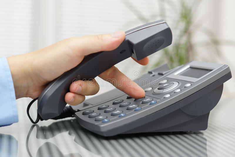 De zakenmanhand draait een telefoonaantal met verbeterd headse royalty-vrije stock afbeeldingen