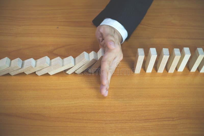 De zakenmanhand houdt domino ononderbroken ten val gebrachte betekenis tegen die bedrijfsmislukking belemmerde Einde over deze be stock afbeeldingen