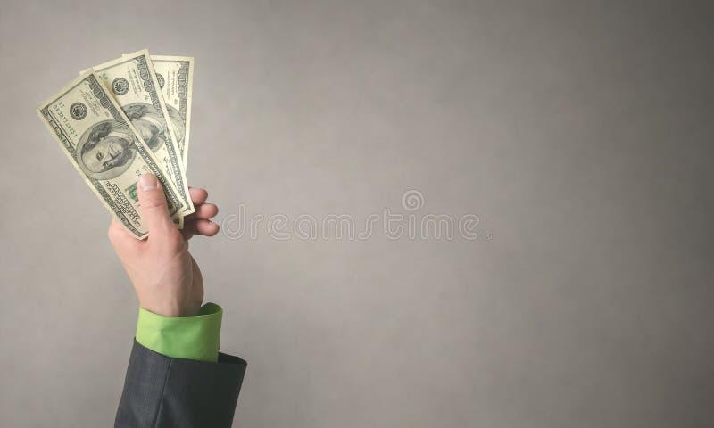 De zakenmanhand rekt een dollarsgeld uit dat op grijze achtergrond met exemplaar ruimteachtergrond wordt geïsoleerd Financiële hu royalty-vrije stock fotografie