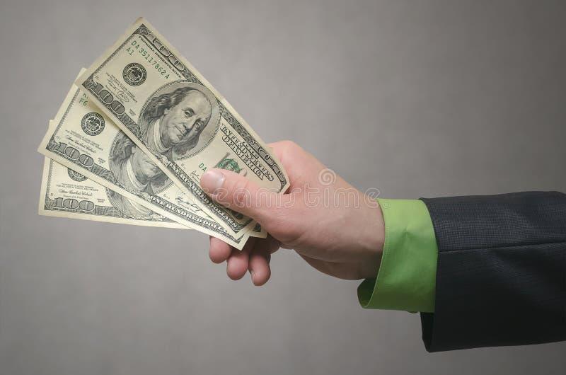 De zakenmanhand rekt een dollarsgeld uit dat op grijze achtergrond met exemplaar ruimteachtergrond wordt geïsoleerd Financiële hu stock foto's