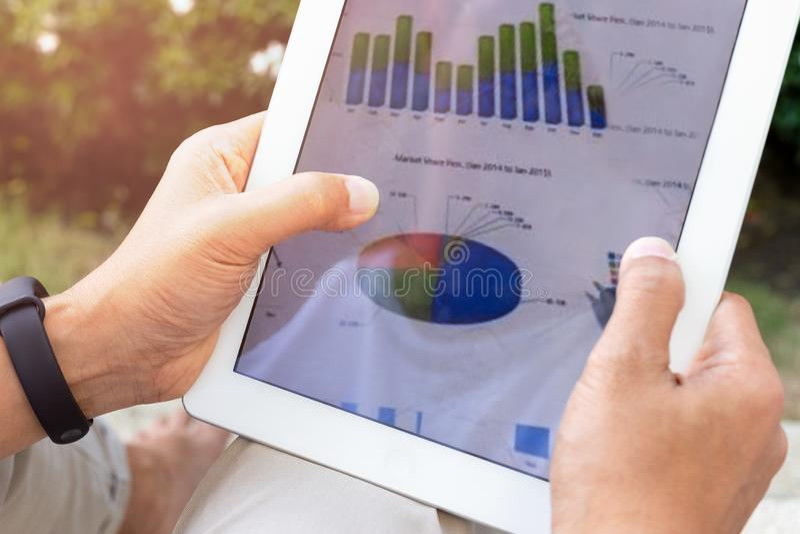 De zakenmanhanden die het tabletscherm met behulp van tonen groene grafiek terwijl wor stock foto