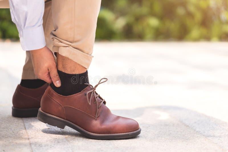 De zakenmanpijn zijn voeten en benen na liep een partij voor zijn wo royalty-vrije stock fotografie