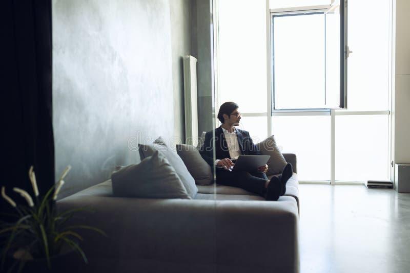 De zakenmanwerken met zijn laptop thuis stock afbeeldingen