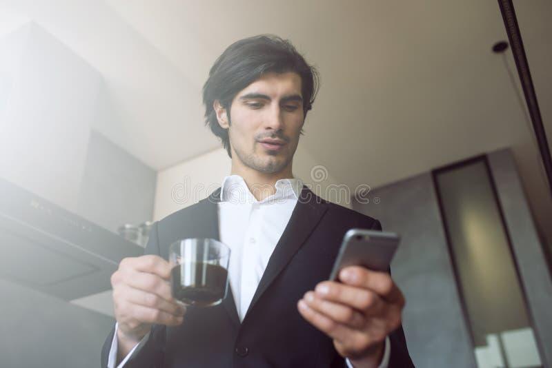 De zakenmanwerken met zijn smartphone thuis royalty-vrije stock fotografie