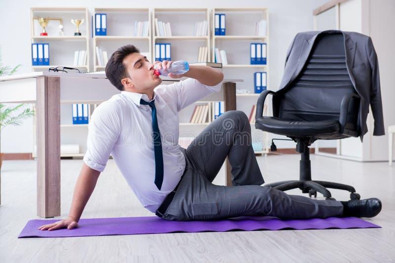 De zakenmanzitting op het vloer drinkwater royalty-vrije stock afbeelding